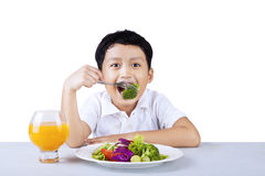 Boy eating broccoli - isolated Stock Image