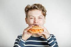 Boy Eating Burger Bun Topped with Shredded Carrots Stock Photography
