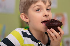 Boy eating caloric muffin Royalty Free Stock Photography