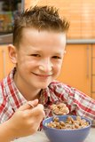 Boy eating cereal. Smiling boy eating a bowl of cereal stock photos