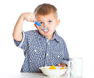 A boy is eating cereal from a bowl. Isolated on a white background Royalty Free Stock Image