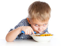 A boy is eating cereal from a bowl Royalty Free Stock Photos