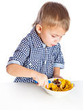 A boy is eating cereal from a bowl Stock Image