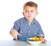 A boy is eating cereal from a bowl Stock Photo