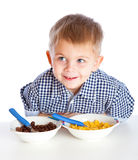 A boy is eating cereal from a bowl Royalty Free Stock Photography