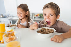 Boy eating cereal next to his sister Stock Photos