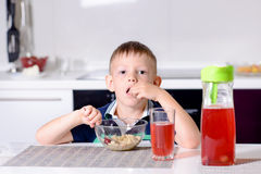 Boy Eating Cherries Off Top of Cereal at Breakfast Royalty Free Stock Photo