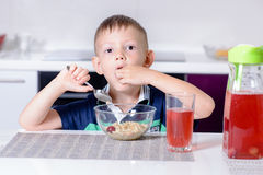 Boy Eating Cherries Off Top of Cereal at Breakfast Stock Photos