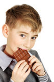 Boy eating a chocolate bar. Young boy eating a chocolate bar over white background Stock Image