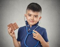 Boy eating chocolate listening to his heart with stethoscope Stock Images