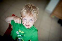 Boy eating chocolate pudding Stock Photography