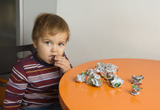 Boy eating chocolates Royalty Free Stock Photos