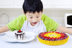 Boy eating colorful desserts at home Royalty Free Stock Images