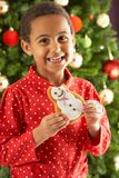 Boy Eating Cookie In Front Of Christmas Tree Stock Photography