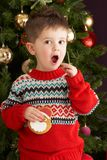 Boy Eating Cookie In Front Of Christmas Tree Royalty Free Stock Photography