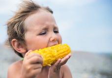 Boy eating corn on the beach Royalty Free Stock Photos