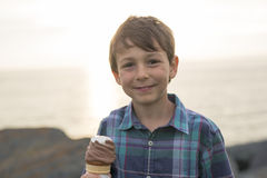 Boy eating a delicious ice cream on the sunset. Stock Image