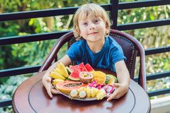 The boy is eating different fruits on the terrace stock images