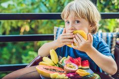 The boy is eating different fruits on the terrace royalty free stock photography