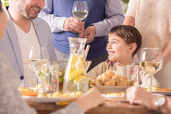 Boy eating dinner with family. Happy, small boy eating dinner with his family Royalty Free Stock Photography