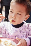 Boy eating dumplings Stock Images