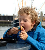 Boy eating Fish in Harbour Royalty Free Stock Photography
