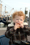 Boy eating Fish in Harbour Stock Photo