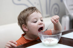 Boy eating flakes in milk Royalty Free Stock Image