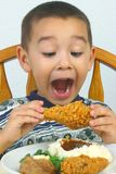 Boy eating fried chicken. A young boy ready to devour his dinner royalty free stock photos