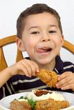 Boy eating fried chicken. A young boy and his dinner of fried chicken, mashed potatoes, and green beans stock photos
