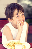 Boy eating fries Stock Photography