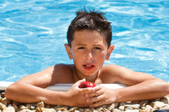 Boy eating fruit in swimming pool Stock Images