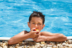 Boy eating fruit in swimming pool Royalty Free Stock Photo