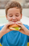 Boy eating hamburger Stock Photo