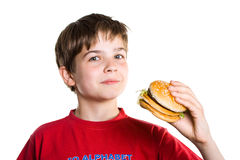The boy eating a hamburger. Stock Photo
