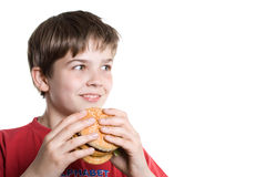 The boy eating a hamburger. Stock Photos
