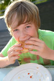 Boy is eating hamburger Stock Photography