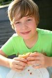 Boy is eating hamburger Royalty Free Stock Photography