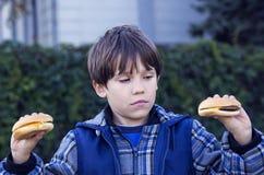 Boy eating a hamburger Stock Image