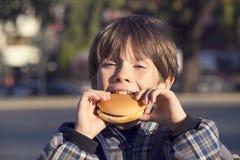 Boy eating a hamburger Royalty Free Stock Images