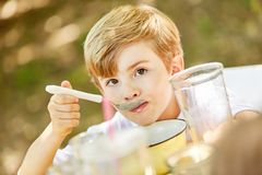 Boy is eating healthy cereal in the morning for breakfast. In kindergarten or at home Royalty Free Stock Photo