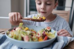 Boy is eating the healthy salad from a large bowl royalty free stock images