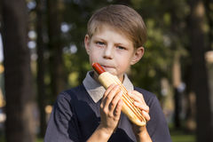 Boy eating a hot dog. On the street Royalty Free Stock Photos