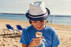 Boy eating ice cream on beach Stock Photo