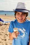 Boy eating ice cream on beach Stock Images