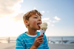 Boy eating an ice cream. Standing near seafront. Little boy on vacation treating himself to an ice cream Stock Photos