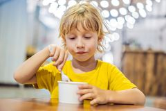 Boy eating ice cream in a cafe stock image