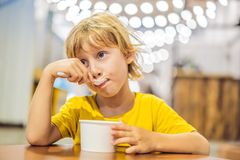Boy eating ice cream in a cafe stock photo
