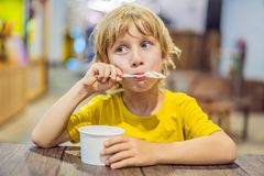 Boy eating ice cream in a cafe stock images