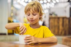 Boy eating ice cream in a cafe royalty free stock photos